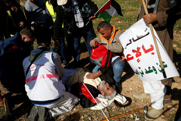 Palestinian lies on the ground after inhaling tear gas fired by Israeli troops during clashes at a protest calling for the release of Palestinian prisoners from Israeli jails near Ramallah