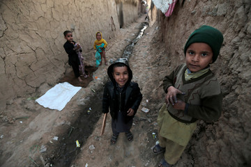 Afghan refugee children pose for a picture as they play in a slum in Islamabad