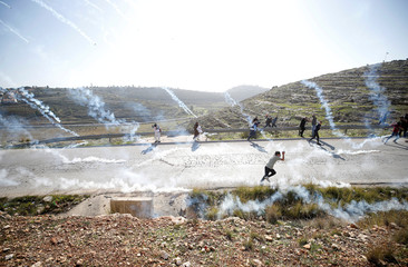 Palestinian demonstrators run as tear gas is fired by Israeli troops during clashes at a protest calling for the release of Palestinian prisoners from Israeli jails near Ramallah
