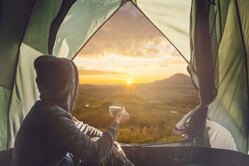 Young woman traveler sitting in the tent, relaxing and drinking coffee with beautiful sunrise