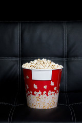 Closeup of a popcorn box on a black leather couch with black background