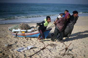 Palestinian fishermen pull a boat at the beach near the border with Egypt, in the southern Gaza Strip