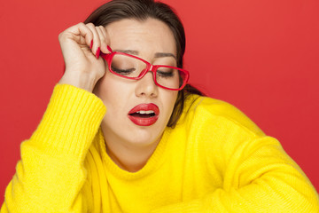 beautiful unhappy woman with red glasses on red background