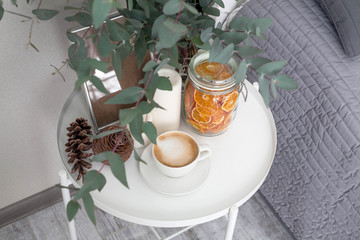 Eucalyptus in the interior, morning coffee on the table in the bedroom by the bed