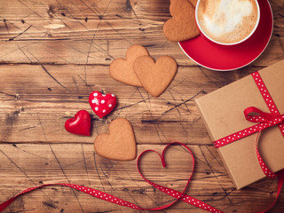 Valentines day background with coffee cup, heart shape cookies and gift box. Top view. Flat lay