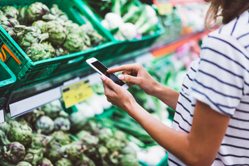 Young woman shopping purchase healthy food in supermarket blur background. girl buy products using smartphone in store. Hipster at grocery using smartphone. Person comparing price at store.