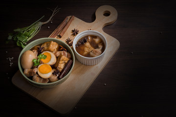 Pha-lo with dim light : Eggs boiled and pork boiled with spices and fried tofu in sweet gravy soup on wooden background with copy space