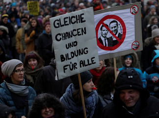 Protesters hold a sign with portraits of Austrian Chancellor Kurz and Vice Chancellor Strache during an anti-government demonstration in Vienna