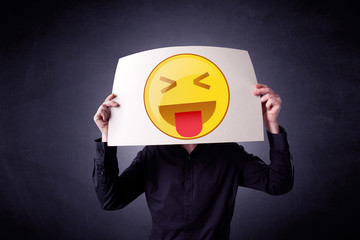 Businessman holding paper with emoticon