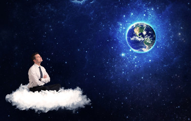 Man sitting on cloud looking at planet earth