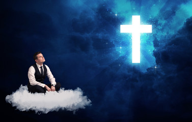 Man sitting on cloud lokking at a cross