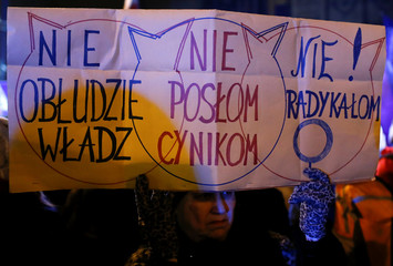 People gather to protest against plans to further restrict abortion laws in front of the Parliament in Warsaw