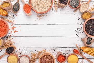 Set of Groats and Grains. Buckwheat, lentils, rice, millet, barley, corn, black rice. On a white wooden background. Top view. Copy space.