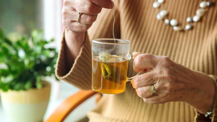 older woman hand holding a glass of tea.