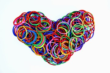 heart shape of colorful rubber ring on white paper background