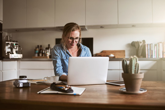 Young woman working online in her kitchen with a laptop
