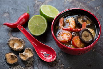 Red bowl with thai Tom Yum soup and some of its cooking components, selective focus, studio shot