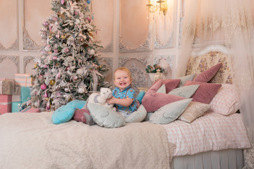 Little happy boy with toys sitting on a bed in a pink room with a Christmas tree