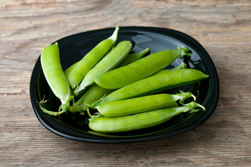 Pods of green peas in plate on wooden background