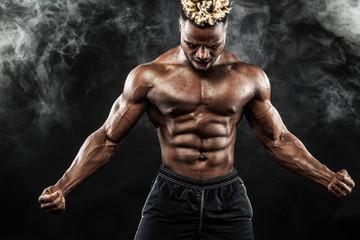 Sports wallpaper on dark background. Power athletic guy bodybuilder.