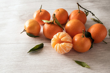 group of clementines with leaves, whole and peeled on a light gray wooden background with copy space