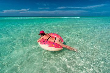 Smiling beautiful brunette woman in pink hat is swimming on a big inflatable tube at the coast of Caribbean Sea