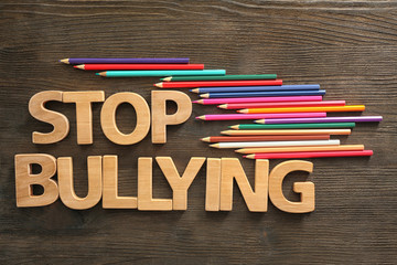 "Text ""Stop bullying"" on wooden background"