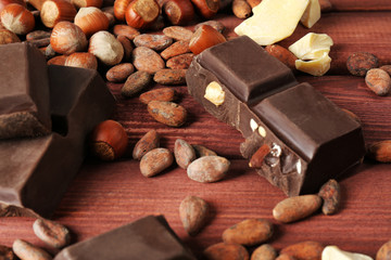 Chocolate, hazelnuts, cocoa beans and butter on wooden background