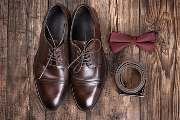 Composition with elegant leather men's shoes on wooden background