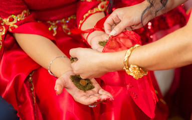 They put their hands henna of the bride . Drawing henna at the Henna party. They put money in their hands