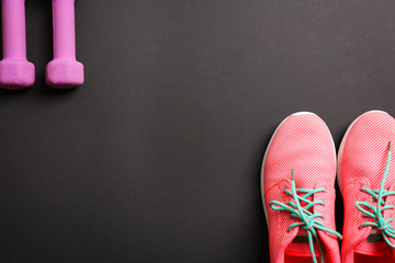 Sneakers and dumbbells with blank space for gym exercise plan on black background. Flat lay composition