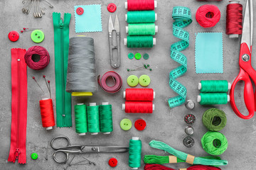 Composition with sewing threads and accessories on grunge background, top view