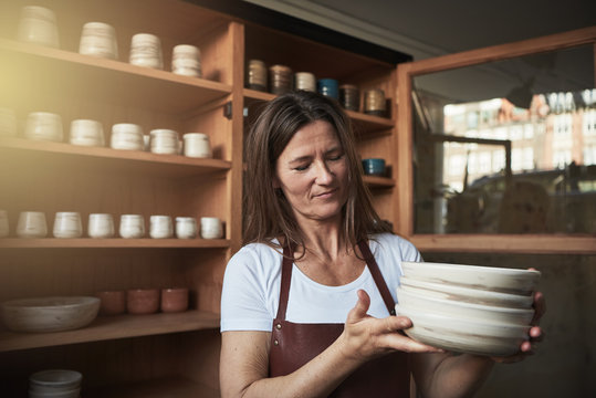 Smiling artisan standing with plates in her pottery gallery