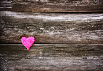 Decorative small heart on wooden old weathered background.
