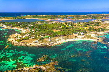 Aerial view of Bathurst Lighthouse and Pinky Beach in Rottnest Island, Australia, on a sunny day. Scenic flight over famous tourist destination of Western Australia. Indian Ocean with reef. Copy space