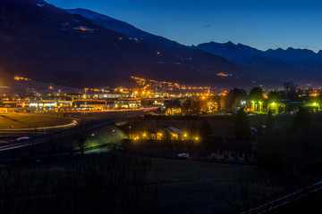 Italian city at blue hour with mountains on background