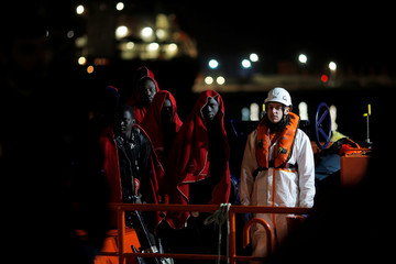 Migrants stand after arriving on a rescue boat at the port of Malaga