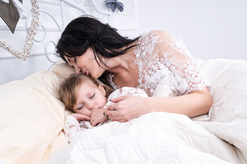 Mom gently kisses the daughter sleeping next to her