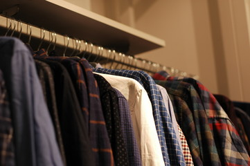 A lot of shirts hang on the hangers in the store.