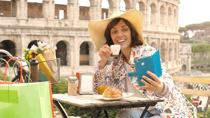 Happy young woman tourist taking selfies with smartphone at the table outside a bar restaurant in front of the Colosseum in Rome with coffee, juice and cornetto. Elegant beautiful dress with large hat