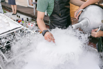 bartenders serve the cocktail in a large bowl with liquid nitrogen. row line of different alcoholic cocktails on a party. wedding day or birthday