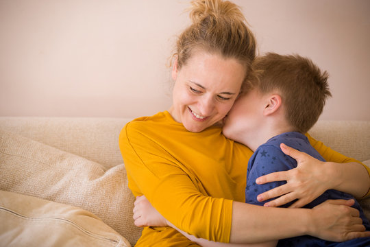 Portrait of young woman with cute kid boy sitting on the sofa at home. Child whispering in mother's ear and making her smile.