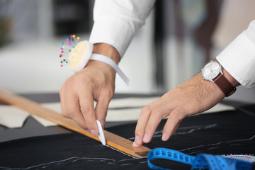 Young tailor marking fabric with chalk in atelier