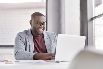 Professional male economist searches needed information on portable computer, happy to recieve high net profit, spends important banking operation. Black male trader analyzes financial market