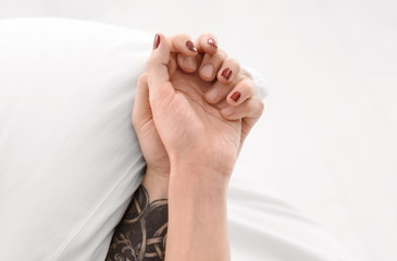 Tattooed man with his girlfriend in bed, closeup