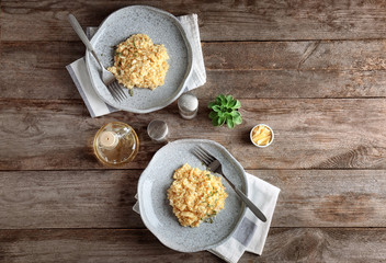 Plates with delicious risotto on wooden table