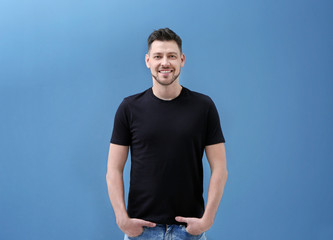 Young man in black t-shirt on color background. Mockup for design