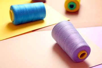 Different sewing threads on color background