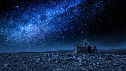 Small stone cottage and milky way at night, Iceland