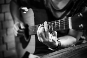 Man wearing watch is playing acoustic guitar in the red bricks background room. , black and white.